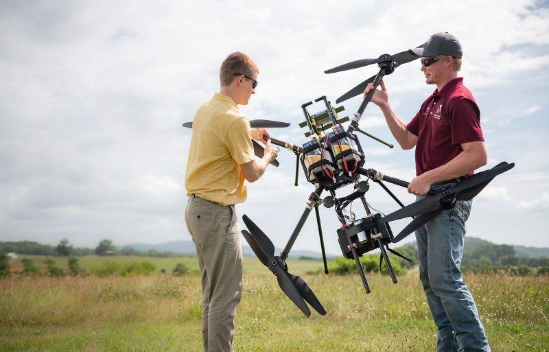 Engineers carry a large quadcopter into a field for testing.